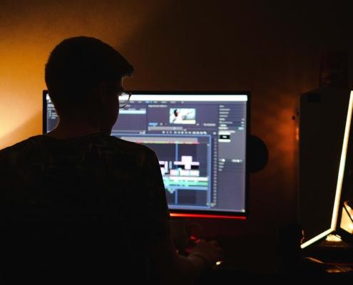 Man at screen editing at home